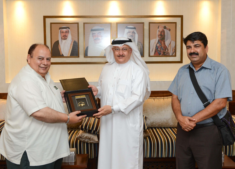 Abdulrahman Askar (centre) presented a memento to Asghar Khan during their meeting ©Bahrain Olympic Committee