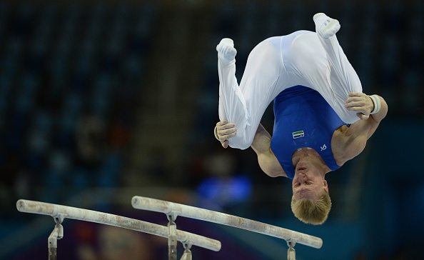 Eduard Shaulov of Uzbekistan in individual qualification and team final action on the parallel bars ©AFP/Getty Images