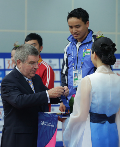 IOC President Thomas Bach presenting Rai Jitu of India with his pistol shooting medal ©AFP/Getty Images