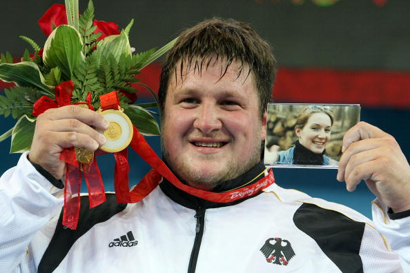 Matthias Steiner posing on the Beijing 2008 podium with a photo of his late wife ©Getty Images