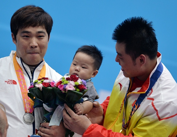 China's Yang Zhe plays with the eight-month old son of South Korea's Kim Min-jae on the weightlifting podium ©AFP/Getty Images