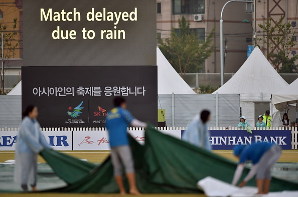 Officials covering the pitch at the cricket ©AFP/Getty Images