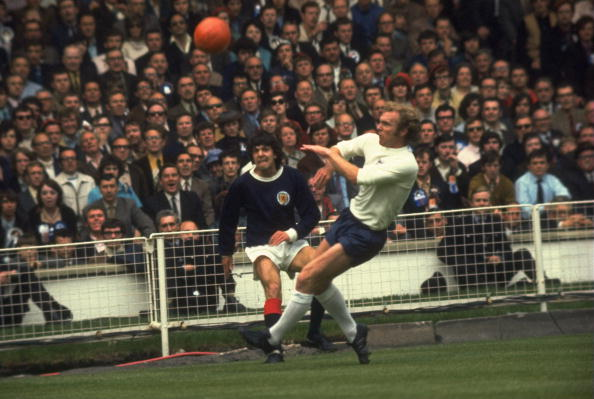 """Scotland's Peter Cormack gets a cross in despite the attentions of Bobby Moore during England's 3-1 win at Wembley in 1971. The Scots sang """"All we are say-ing is give us a goal"""", to the tune of John Lennon's Give Peace A Chance. But Scotland only managed one of those in five successive games against the Auld Enemy in the early 1970s ©Allsport/Getty Images"""