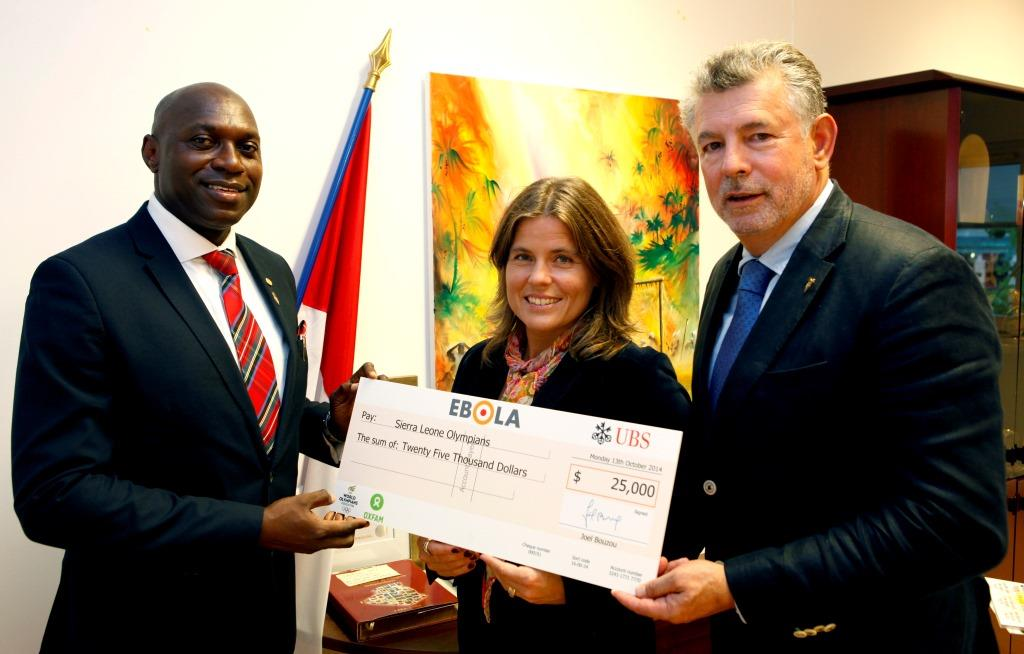 Joël Bouzou (right), WOA President, and Pernilla Wiberg (centre), two-time Olympic gold medallist, present Dr Francis Dove Edwin (left) with funding for the first #TargetEbola container of supplies ©WOA