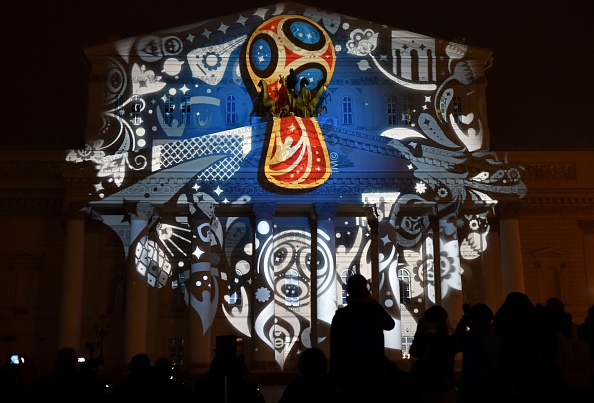 People watch as the facade of the historical Bolshoi Theatre is illuminated with the official emblem of the 2018 FIFA World Cup ©Getty Images