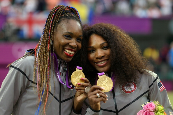 Serena and Venus Williams celebrate winning the women's doubles at London 2012, the fourth Olympic gold medal for each player ©Getty Images