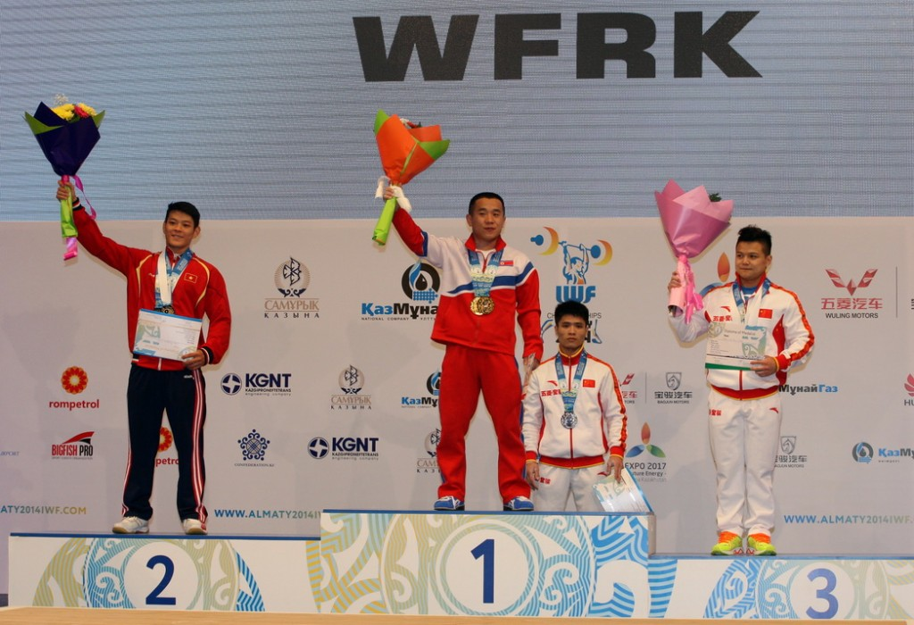 North Korea's Om Yun Chol celebrates his gold medal at the IWF World Weightlifting Championships in Almaty alongside silver medallist, Vietnam's Kim Tuan Thach, and bronze medallist, China's Long Qingquan