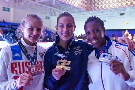 Elin Johansson (centre) celebrates her gold medal with silver medallist Haby Niare (right) and bronze medallist Anastasiia Baryshnikova (left) ©WTF