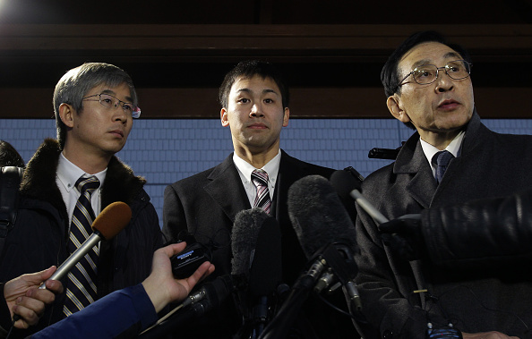Japanese swimmer Naoya Tomita (centre) speaks to the media after appearing in court, accused of stealing a camera during the Asian Games ©Getty Images