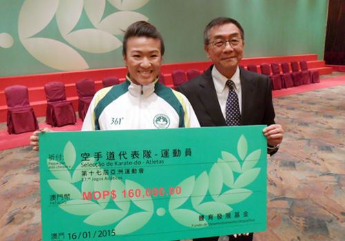 Paula Carion, who won a bronze medal in karate at the 2014 Asian Games, accepts the reward for her achievement from Sports and Olympic Committee of Macau President Charles Lo Keng Chio ©OCA