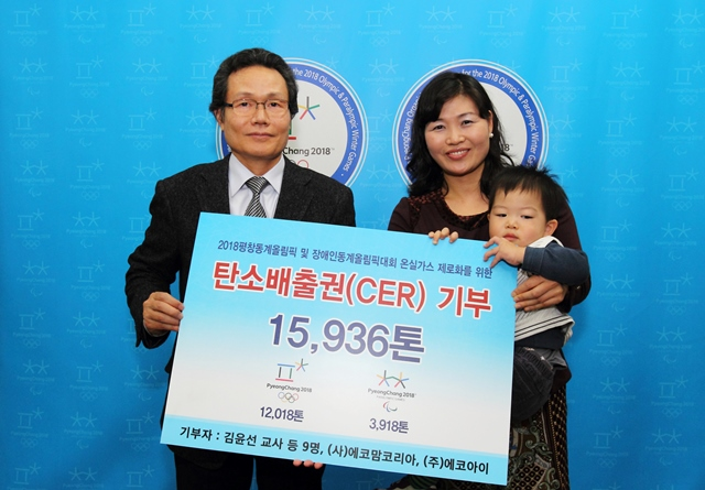 Sangpyo Kim (left), POCOG vice-president of venues and infrastructure, accepts the CERs contribution certificate from Youn-sun Kim (right), a teacher at Yeonhui Elementary School ©POCOG