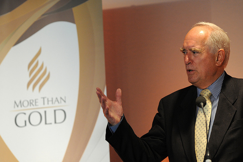 Brian_Mawhinney_in_front_of_More_than_Gold_logo