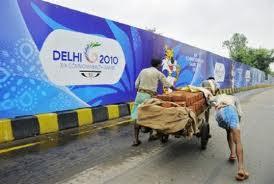 Delhi_workmen_go_past_Commonwealth_Games_sign