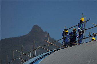 Maracana_with_workman_on_top_of_roof_and_Sugar_Loaf_Mountain_in_background
