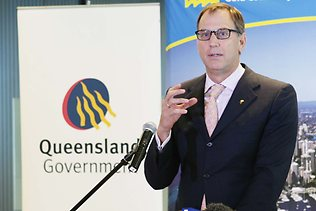 Mark_Stockwell_in_front_of_Queensland_logo