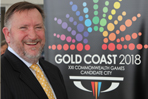 Mike_Hooper_in_front_of_Gold_Coast_logo